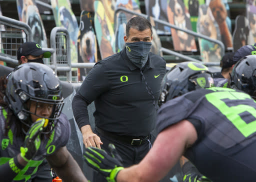 Oregon head coach Mario Cristobal watches his offensive linemen warm up before an NCAA college football game against UCLA, Saturday, Nov. 21, 2020, in Eugene, Ore. (AP Photo/Chris Pietsch)
