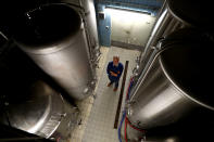 In this photo taken Friday, May 1, 2020 brewer Karlmann Detter poses between brewery tanks in his 120 year old family brewery in Altoetting, Germany. The 'Graminger Weissbraeu' brewery, which has been in the same family for a century, is preparing to welcome guests back to its restaurant for the first time in two months — with new rules and fears for the future. (AP Photo/Matthias Schrader)