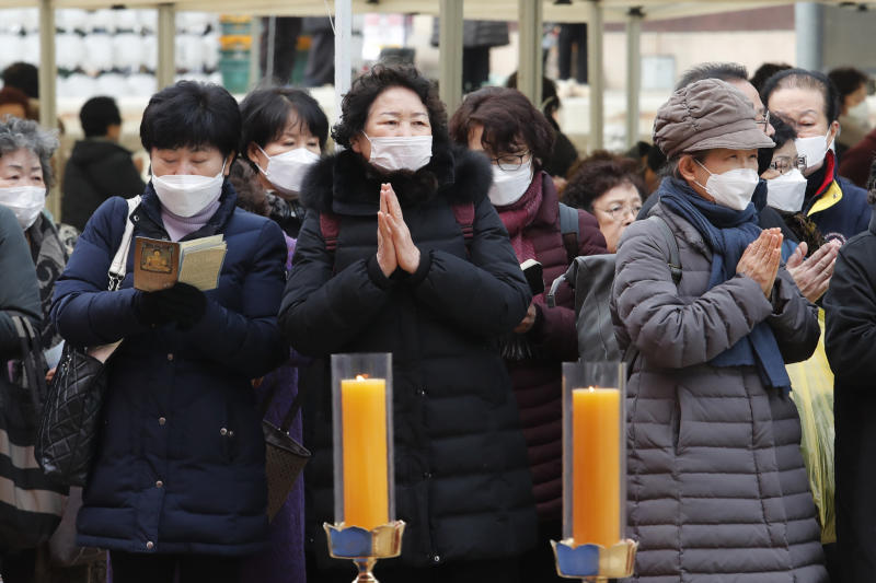 People wearing face masks pray at the Jogyesa Buddhist temple in Seoul, South Korea, Sunday, Feb. 2, 2020. This weekend, South Korea and India flew hundreds of their citizens out of Wuhan, the city at the center of an area where some 50 million people are prevented from leaving in a sweeping anti-virus effort. (AP Photo/Ahn Young-joon)
