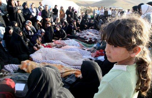 Iranians mourn over the covered bodies of loved ones in the village Baje-Baj, near the town of Varzaqan. Iran on Sunday stepped up relief operations in shattered villages in its northeast after saying rescue operations were completed following a double earthquake which cost 227 lives and injured 1,380 people