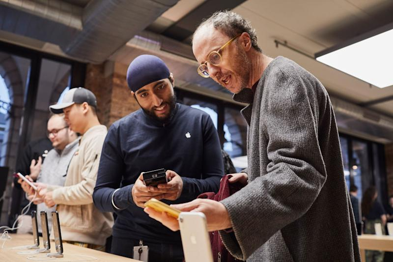 An Apple store employee with a customer at an in-store iPhone display.