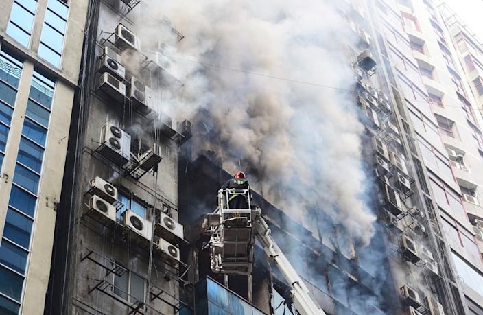A firefighter works to douse a fire in a multi-storied office building in Dhaka, Bangladesh, March 28, 2019.  (AP Photo/Mahmud Hossain Opu)