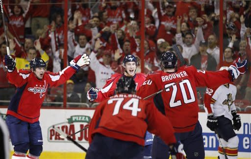 Washington Capitals center Jay Beagle, center, celebrates with left wing Matt Hendricks, left, defenseman John Carlson (74), and left wing Troy Brouwer (20) after scoring a goal during the first period of an NHL hockey game against the Florida Panthers on Thursday, April 5, 2012, in Washington. (AP Photo/Evan Vucci)