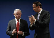 Attorney General Jeff Sessions is applauded by Deputy Attorney General Rod Rosenstein during a news conference at the U.S. Attorney's Office for the District of Columbia in Washington, Monday, Oct. 15, 2018, to announce on efforts to reduce transnational crime. (AP Photo/Carolyn Kaster)