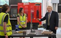 Britain's Prime Minister Boris Johnson gestures as he speaks with construction apprentices at The Dudley Institute of Technology in Dudley