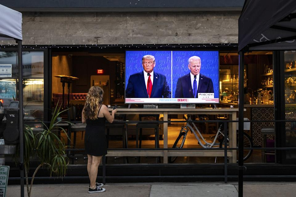A waitress with a remote standing in front of a TV showing the debate set up in the window of a restaurant