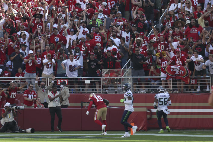 Fans cheer as San Francisco 49ers wide receiver Deebo Samuel (19) scores against the Seattle Seahawks during the second half of an NFL football game in Santa Clara, Calif., Sunday, Oct. 3, 2021. (AP Photo/Jed Jacobsohn)