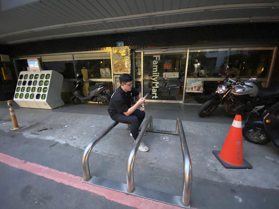 A convenience store worker sits outside the darkened store during a blackout in New Taipei City in Taiwan on Thursday, May 13, 2021. An equipment failure has caused an outage at a power plant in southern Taiwan, triggering rolling blackouts across the island affecting millions of people. (AP Photo/Johnson Lai)