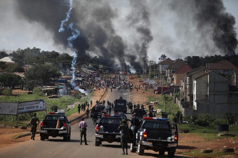 Nigerian Police fire teargas at people during clashes between youths in Apo, Abuja, Nigeria - AFP