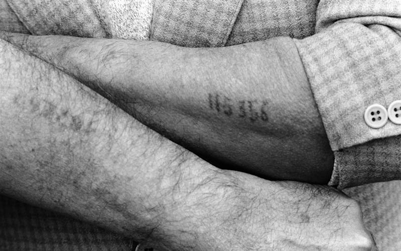 A Holocaust survivor displays the numerical tattoo stamped on his arm, a physical remnant of his imprisonment in a World War II Nazi concentration camp, during ceremonies commemorating the 50th annivesary of the Warsaw Ghetto Uprising in 1943. - Ira Nowinski/Ira Nowinski