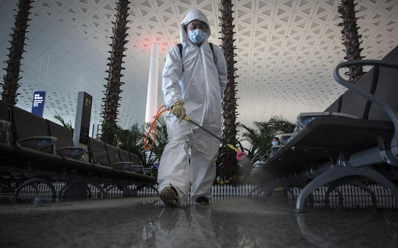 Staff disinfect a seating area at Tianhe airport in Wuhan - Getty