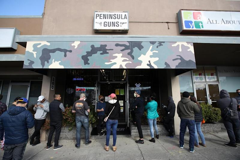 People wait in line to purchase guns and ammunition in San Bruno, California.