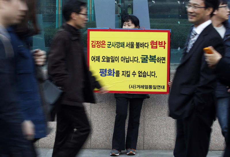 """A North Korean defector protests against North Korea's threat for war as South Koreans pass by on a street in Seoul, South Korea, Saturday, March 9, 2013. Nearly two decades ago, South Koreans cleared store shelves after a North Korean threat to turn Seoul into a """"sea of fire"""" raised war panic. On Saturday, South Koreans expressed some fear but mostly apathy and restraint after a week of warlike rhetoric from the North, including another """"sea of fire"""" vow. The letters read """" When South Koreans submit to threat by North Korean leader Kim Jong Un, we cannot keep the peace."""" (AP Photo/Ahn Young-joon)"""
