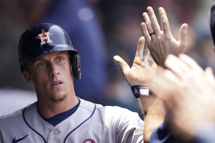 Houston Astros' Myles Straw is congratulated by teammates after scoring in the fourth inning of a baseball game against the Cleveland Indians, Sunday, July 4, 2021, in Cleveland. (AP Photo/Tony Dejak)