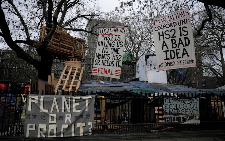 Anti-High Speed 2 (HS2) rail line protest banners are displayed in the Euston Square Gardens tree protection camp - AP