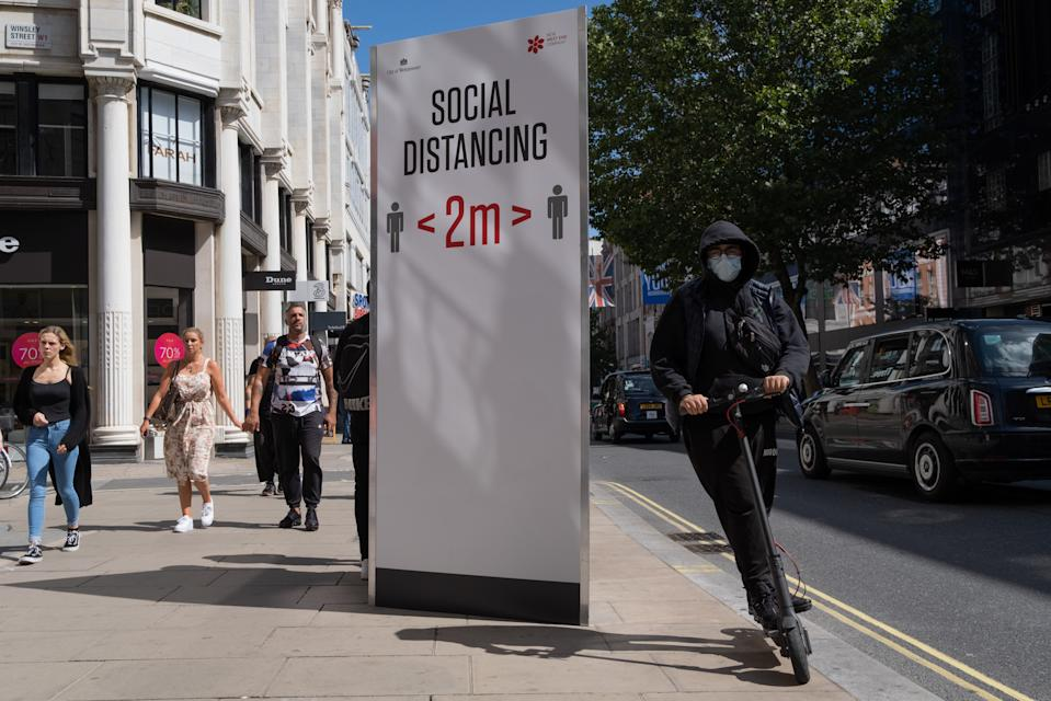 A man riding an eScooter speeds past a social distance board on Oxford Street during the Coronavirus pandemic, on 20th August 2020, in London, England. (Richard Baker / In Pictures via Getty Images)