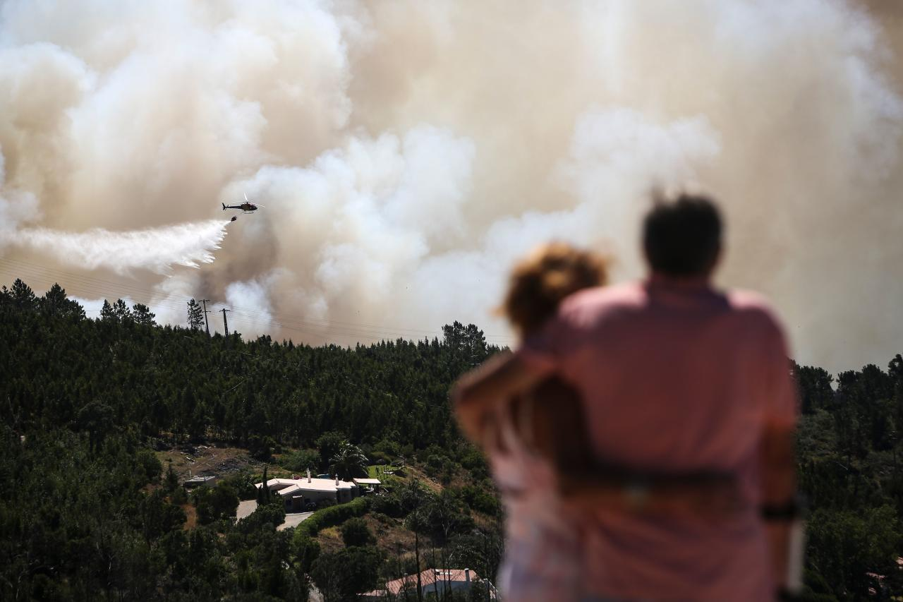 <p>A couple watches an helicopter dropping water on a wildfire near Monchique, in Algarve, on Aug. 8, 2018. Spain and Portugal approached record temperatures at the weekend, with the mercury hitting 46.6 degrees Celsius (116 Fahrenheit) at El Granado in Spain and 46.4 C in Alvega, Portugal, according to the World Meteorological Organisation (WMO). While the deadly hot spell is expected to ease in parts of western Europe in the coming days, firefighters in Spain and Portugal struggled to contain wildfires that have swept southern areas. (Photo: Carlos Costa/AFP/Getty Images) </p>