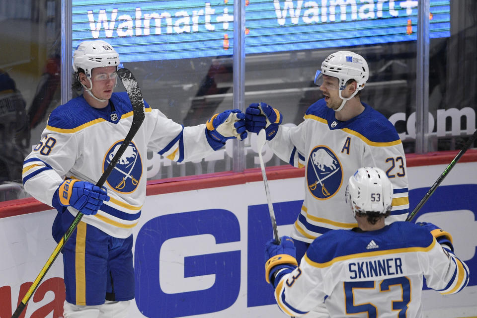Buffalo Sabres left wing Victor Olofsson (68) celebrates his goal with right wing Sam Reinhart (23) and left wing Jeff Skinner (53) during the second period of the team's NHL hockey game against the Washington Capitals, Thursday, April 15, 2021, in Washington. (AP Photo/Nick Wass)