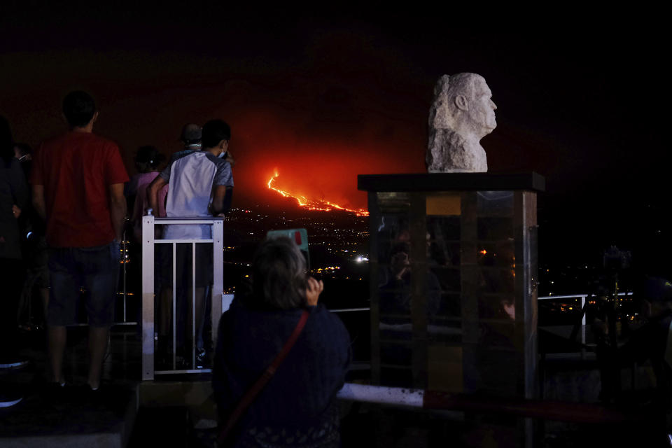 People watch the volcano as it continues to spew lava on the Canary island of La Palma, Spain on Saturday, Oct. 9, 2021. A new river of lava has belched out from the La Palma volcano, spreading more destruction on the Atlantic Ocean island where molten rock streams have already engulfed over 1,000 buildings. The partial collapse of the volcanic cone has sent a new lava stream heading toward the western shore of the island. (AP Photo/Daniel Roca)