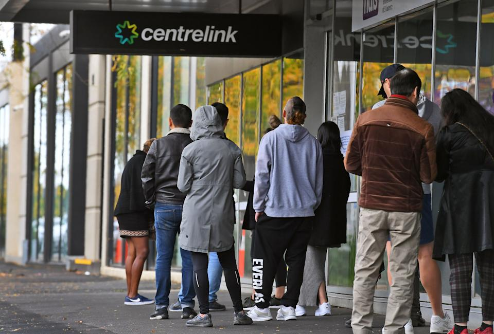 People queue up outside a Centrelink office in Melbourne on April 20, 2020, which delivers a range of government payments and services for retirees, the unemployed, families, carers and parents amongst others. -