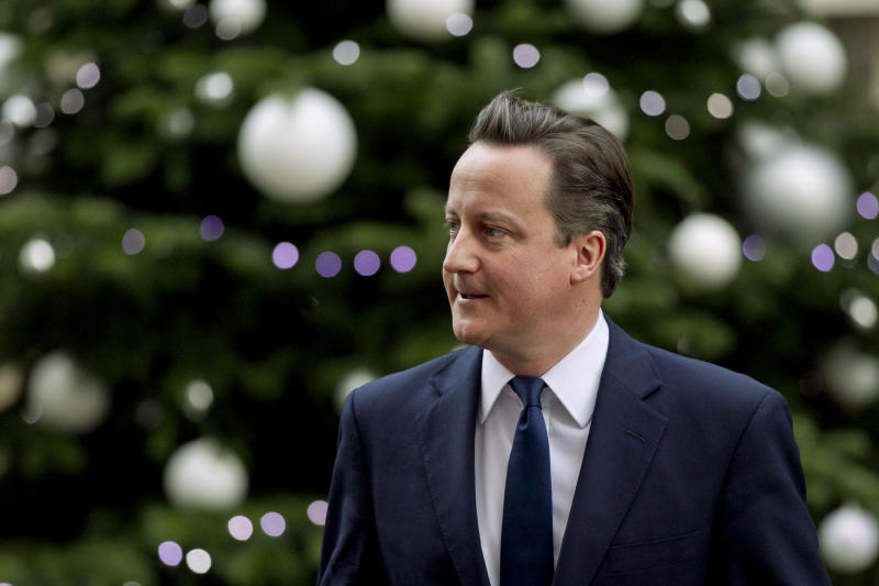 Britain's Prime Minister David Cameron walks past the Downing Street Christmas tree as he leaves number 10 in London, to go to the weekly Prime Minister's Questions session at the Houses of Parliament, Wednesday, Dec. 7, 2011.  (AP Photo/Matt Dunham)