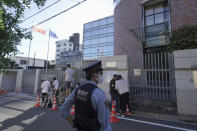 A Japanese police officer stands by media crews in front of the Embassy of Poland in Tokyo where the Belarusian athlete Krystsina Tsimanouskaya who seeks asylum is staying, Tuesday, Aug. 3, 2021. Tsimanouskaya waged - and lost - a legal fight to run in the 200 meters at the Olympics while she was also seeking a humanitarian visa to leave the Tokyo Games safely. (AP Photo/Kantaro Komiya)
