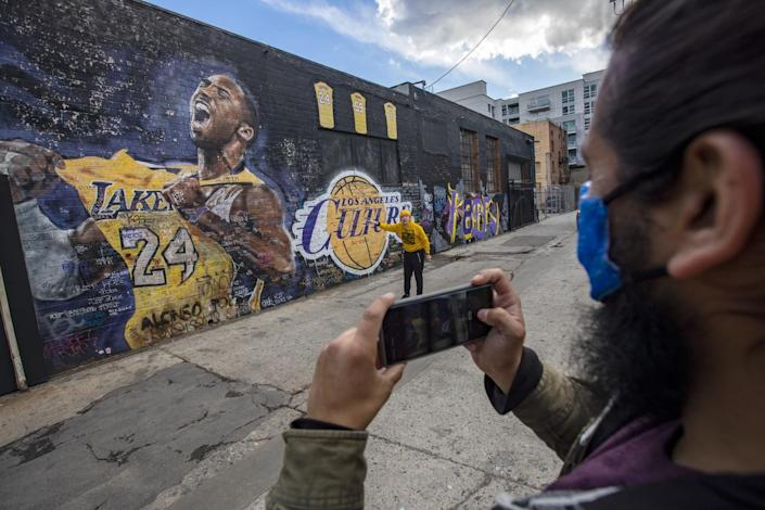 A man holds up his cellphone to take a picture of another man in front of a mural of Kobe Bryant in a Lakers uniform.