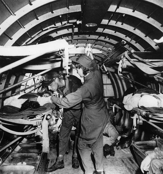 FILE - This June 4, 1943 black-and-white file photo shows a wounded U.S. Marine is given a plasma transfusion by nurse Mae Olson aboard an aerial evacuation unit, over Guadalcanal, Solomon Islands. Women served and died on the nation's battlefields from the first. They were nurses and cooks, spies and couriers in the Revolutionary War. Some disguised themselves as men to fight for the Union or the Confederacy. Yet the U.S. military's official acceptance of women in combat took more than two centuries. New roles for females were doled out fitfully _ whenever commanders got in a bind and realized they needed women's help. A look at milestones on the way to lifting the ban on women in ground combat. (AP Photo, File)