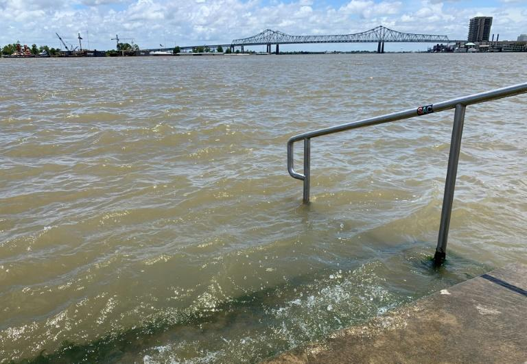 The swollen Mississippi River laps at the stairs on a protective levee in New Orleans (AFP Photo/Michael Mathes)