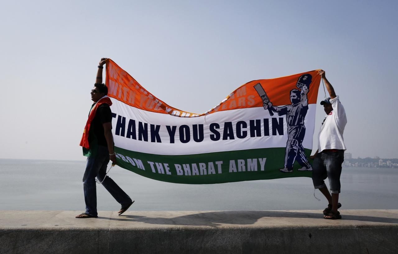 Cricket fans walk on a sea wall while holding a banner in tribute to Indian cricketer Sachin Tendulkar outside a stadium in Mumbai November 16, 2013. Tendulkar did not get a chance to bat again in his final test but India's 'Little Master' was allowed to bowl a couple of overs on Saturday before drawing his 24-year glittering career to an emotional conclusion. REUTERS/Danish Siddiqui (INDIA - Tags: SPORT CRICKET)