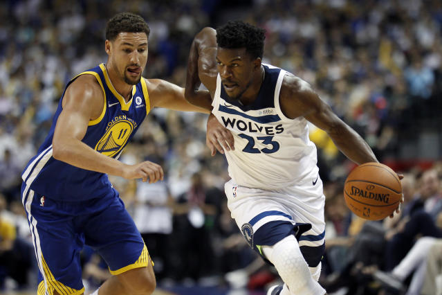 The Timberwolves' Jimmy Butler, right, drives past the Warriors' Klay Thompson during a preseason game. (AP)