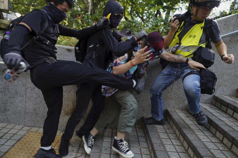 Protesters attack a man who was trying to stop them for vandalizing near the Tsim She Tsui police station during a rally in Hong Kong, Sunday, Oct. 20, 2019. Hong Kong protesters again flooded streets on Sunday, ignoring a police ban on the rally and demanding the government meet their demands for accountability and political rights. (AP Photo/Vincent Yu)