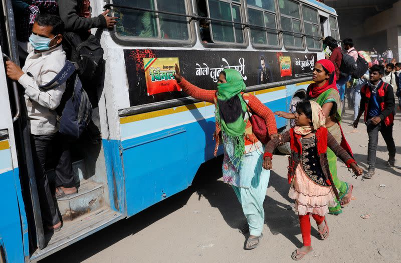 A migrant worker holds her daughter's hand as she tries to board a crowded bus to return to her village, during a 21-day nationwide lockdown to limit the spreading of coronavirus disease (COVID-19), in Ghaziabad