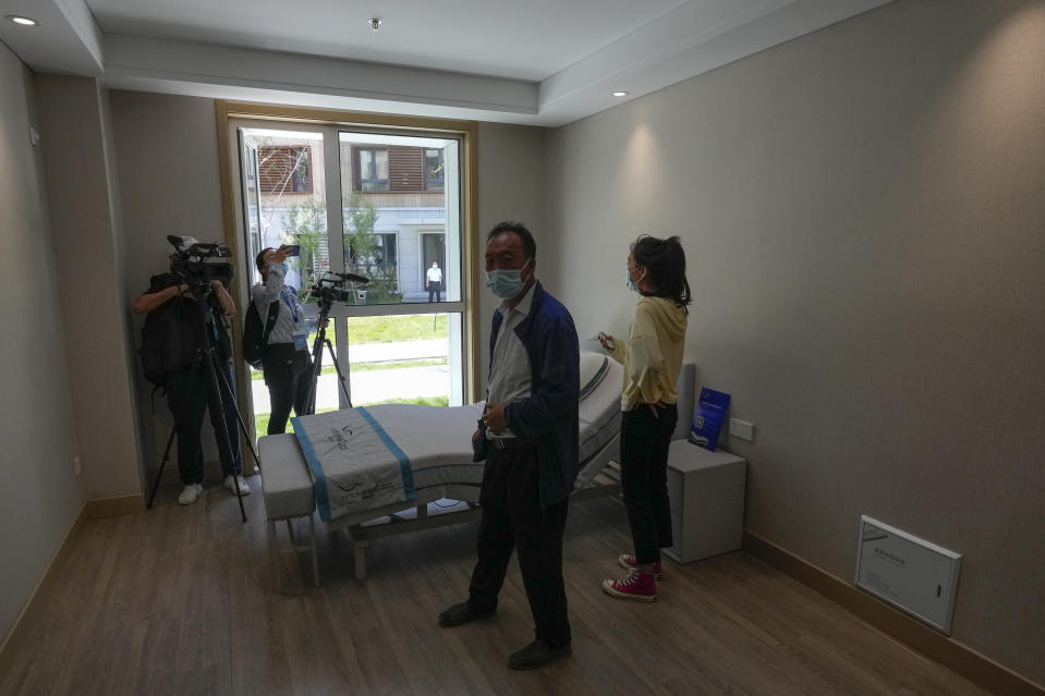 Journalists film an electric-powered bed for athletes at the Olympics Village for Beijing 2022 Olympic and Paralympic Winter Games and Paralympic Winter Games, during a media tour in Zhangjiakou in northwestern China's Hebei province on Wednesday, July 14, 2021. (AP Photo/Andy Wong)