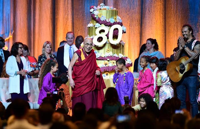 The Dalai Lama reacts as his birthday cake is wheeled out on stage following a performance for him by children at the Honda Center in Anaheim, California, on July 5, 2015 (AFP Photo/Frederic J. Brown)