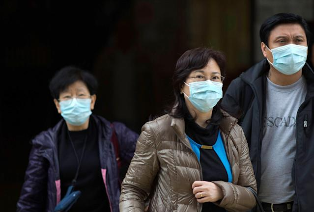 HONG KONG - APRIL 12: People wear face masks outside the Princess Margaret Hospital on April 12, 2013 in Hong Kong. Local authorities have stepped up the testing of live poultry imports from China to include a rapid test for the H7N9 'bird flu' virus. Measures were put in place as the tenth victim of the influenza strain was confirmed in mainland China yesterday. (Photo by Lam Yik Fei/Getty Images)