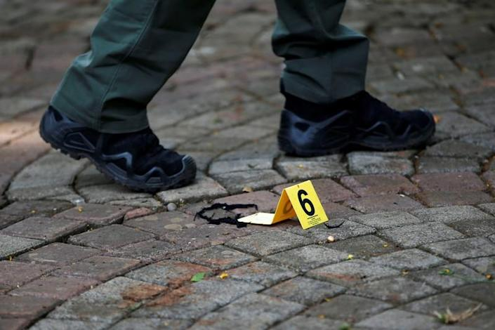 An Indonesian forensic policeman walks past an evidence marker as he investigates a blast at National Monument (Monas) complex in Jakarta