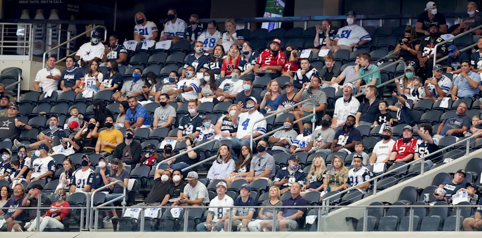 Fans in a section at AT&T Stadium varying between wearing and not wearing masks with very few empty seats between them.