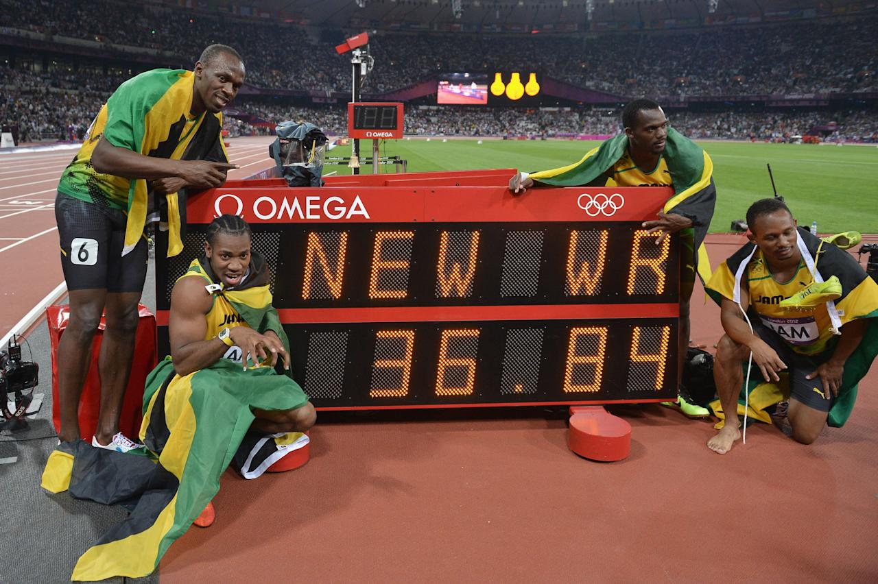 LONDON, ENGLAND - AUGUST 11:  Usain Bolt, Yohan Blake, Michael Frater and Nesta Carter of Jamaica celebrate next to the clock after winning gold and setting a new world record of 36.84 during the Men's 4 x 100m Relay Final on Day 15 of the London 2012 Olympic Games at Olympic Stadium on August 11, 2012 in London, England.  (Photo by Stu Forster/Getty Images)