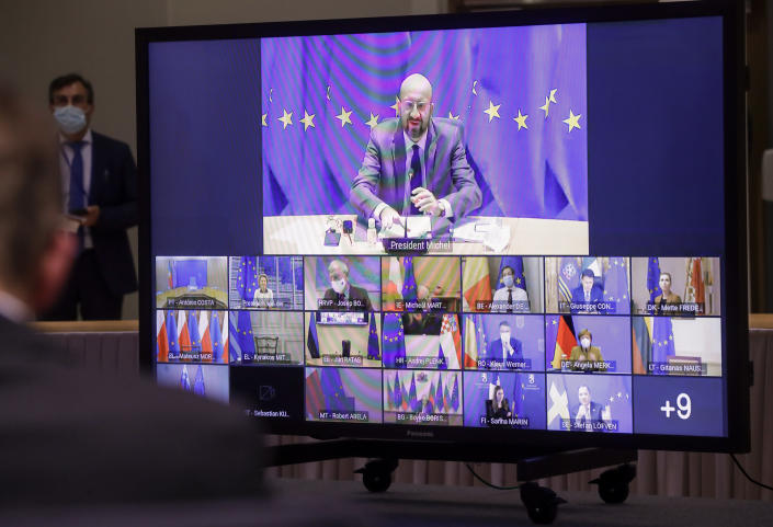 European Council President Charles Michel, top, and European leaders are shown on screen during a EU summit video conference at the European Council headquarters in Brussels, Thursday, Jan. 21, 2021. Worried that the new coronavirus variants could result in another surge of deaths across the European Union and push hospitals to the verge of collapse, EU leaders will assess in a video summit Thursday such measures as further border restrictions, better tracking of mutations and improving coordination of lockdowns. (Oliver Hoslet, Pool Photo via AP)