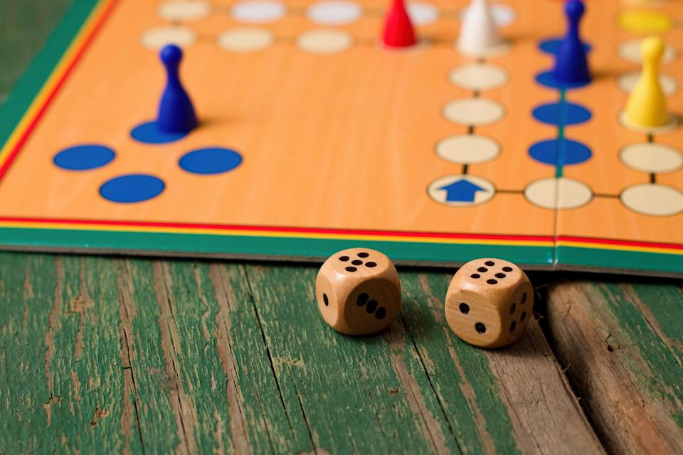 Horizontal photo of Two wooden dices in front of ludo with figurines. Dices have numbers five and six up and all is placed on green old worn wooden board.