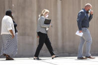 """Aubrey """"Bart"""" Willis, right, and Carolyn Johnson, left, exit the Thad Cochran United States Courthouse in Jackson, Miss., Thursday, Aug. 6, 2020, accompanied by their attorney Bethany Johnson, center, after their arraignment in federal court on immigration crimes and other federal charges stemming from the largest single-state worksite enforcement action last year at a number of Mississippi poultry processing plants. (AP Photo/Rogelio V. Solis)"""