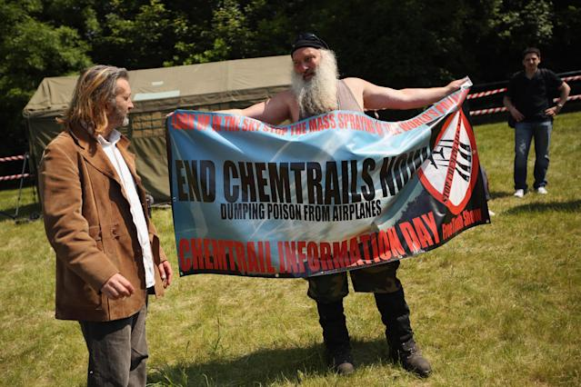 """WATFORD, ENGLAND - JUNE 06: A man demonstrates against """"Chemtrails"""" in a protester encampment outside The Grove hotel, which is hosting the annual Bilderberg conference, on June 6, 2013 in Watford, England. The traditionally secretive conference, which has taken place since 1954, is expected to be attended by politicians, bank bosses, businessman and European royalty. (Photo by Oli Scarff/Getty Images)"""