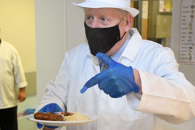 Boris Johnson gestures as he holds a plate of cooked food during his visit to Royal Berkshire NHS Hospital