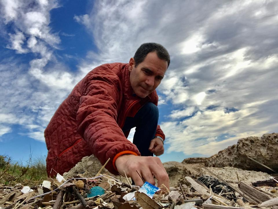 Jace Tunnell, director of the Mission-Aransas National Estuarine Research Reserve at the University of Texas Marine Science Institute, sifts through trash on the beach on Mustang Island in Texas.