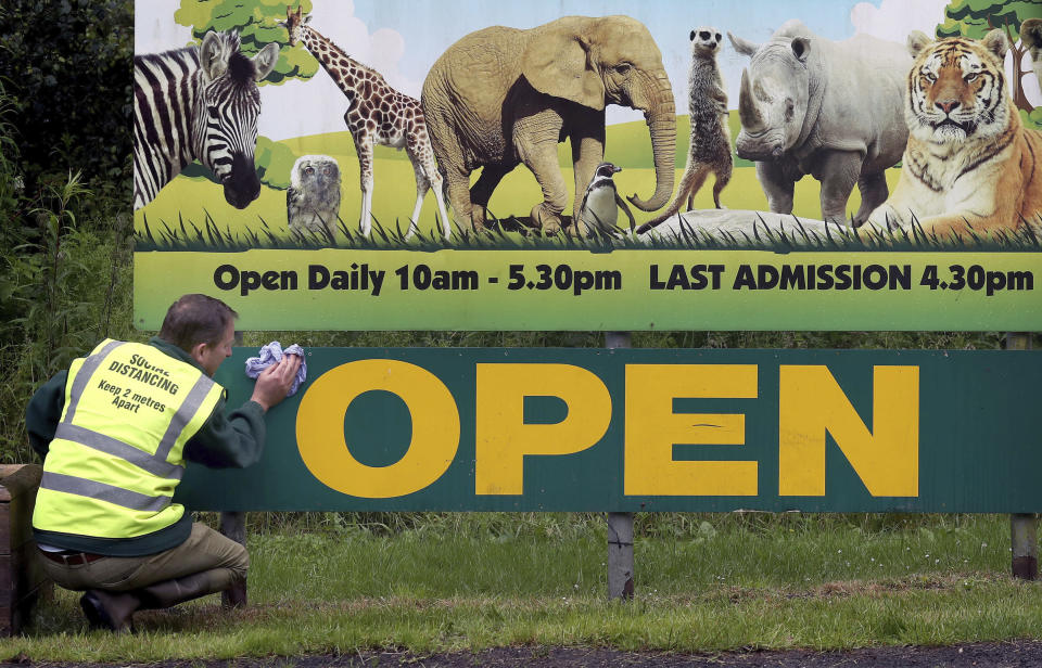 Gary Gilmour wipes an entrance sign to Blair Drummond Safari Park near Stirling, Scotland, Sunday June 28, 2020, where staff are preparing to open the attraction on June 29. Animal parks are set to open along with some other businesses, as part of Scotland's phased release of the coronavirus pandemic lockdown. (Andrew Milligan/PA via AP)