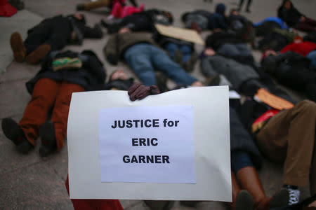 "A protester, demanding justice for Eric Garner, holds a placard while staging a ""die-in"" with dozens of others in downtown White Plains,  New York December 5, 2014.  REUTERS/Adrees Latif/Files"