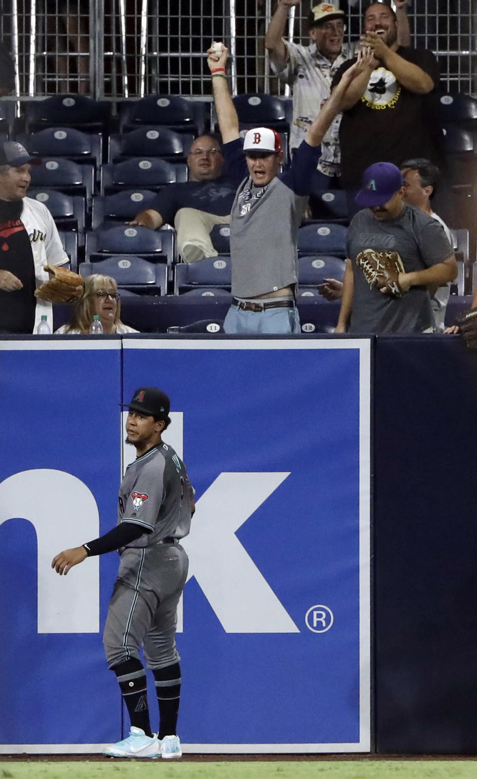 A fan reacts after catching a home run ball hit by the San Diego Padres' Manuel Margot as Arizona Diamondbacks center fielder Jon Jay, below, looks on during the eighth inning of a baseball game Friday, Aug. 17, 2018, in San Diego. (AP Photo/Gregory Bull)