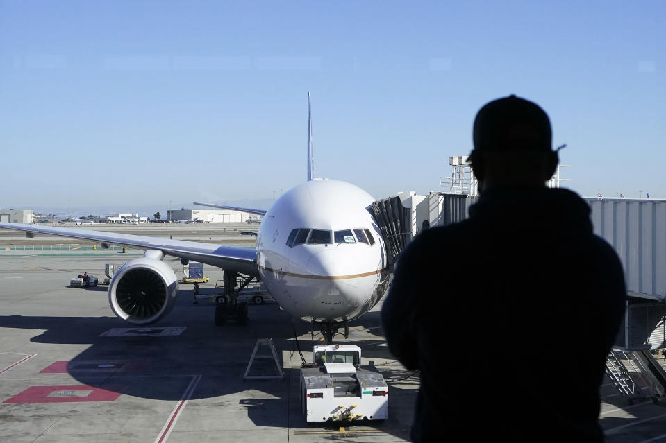 A man looks out of a window toward a United Airlines flight destined for Hawaii at San Francisco International Airport in San Francisco, Thursday, Oct. 15, 2020. Coronavirus weary residents and struggling business owners in Hawaii will be watching closely as tourists begin to return to the islands on Thursday without having to self-quarantine upon arrival. (AP Photo/Jeff Chiu)