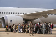 Afghan people who were transported from Afghanistan, walk after disembarking a plane, at the Torrejon military base as part of the evacuation process in Madrid, Monday. Aug. 23, 2021. (AP Photo/Andrea Comas)